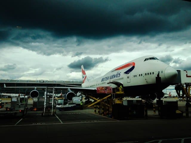 British Airways Boeing 747 being loaded on the ramp being loaded with cargo for take-off.